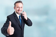 Trustworthy handsome manager talking on cellphone and showing th Royalty Free Stock Image