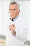 Trustworthy medical doctor. Confident mature doctor holding a st Stock Photography