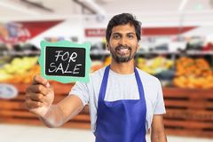 Supermarket employee presenting board with for sale text. Trustworthy supermarket or hypermarket indian male employee presenting blackboard with for sale chalk stock photography