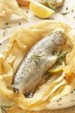 Truta cozida no pergaminho com limão e ro Imagem de Stock