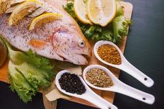Truta fresca e ingredientes para preparar pratos de peixes na tabela preta Fotos de Stock