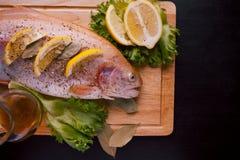 Truta fresca e ingredientes para preparar pratos de peixes na tabela preta Foto de Stock