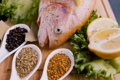 Truta fresca e ingredientes para preparar pratos de peixes na tabela preta Fotos de Stock Royalty Free