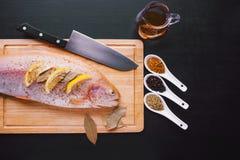 Truta fresca e ingredientes para preparar pratos de peixes na tabela preta Fotografia de Stock Royalty Free