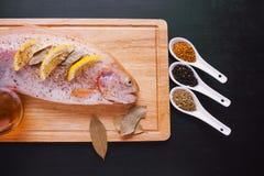 Truta fresca e ingredientes para preparar pratos de peixes na tabela preta Imagem de Stock Royalty Free