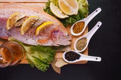 Truta fresca e ingredientes para preparar pratos de peixes na tabela preta Imagens de Stock Royalty Free