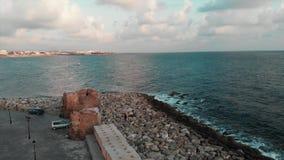 Truteń ląduje przy marina z morzem i niebieskim niebem na tle przy pogodnym letnim dniem Widok z lotu ptaka skalista plaża z ocea zdjęcie wideo