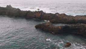 Truteń lata nad mężczyzną który stoi przy krawędzią powulkaniczna skała Tenerife, Hiszpania zbiory wideo