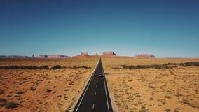 Truteń podąża srebnego samochodowego jeżdżenie wzdłuż sławnej pogodnej amerykanin pustyni autostrady drogi w zabytkach Dolinnych  zbiory wideo
