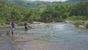 Truteń Pokazuje mężczyzna Łowi z siecią przeciw średniogórzu w rzece zbiory