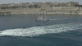 Truteń starannie okrążający wokoło łodzi na tle, widzii Valletta, Malta Stary, miasto - 4K zbiory wideo
