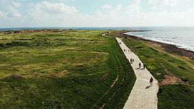 Truteń strzelał pedestrians chodzi i biega wzdłuż seashore linii brzegowej Silne fale uderza skalistą plażę Paphos Cypr zbiory wideo