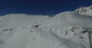 Truteń usuwa narciarskiego skłon z narciarskim dźwignięciem i grupą ludzi na górze grani zbiory wideo