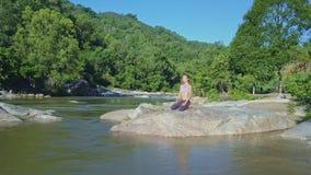 Truteń Usuwa od dziewczyny w joga pozie przy rzeką wśród zwrotników zbiory