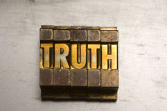 Truth. Brass / Gold colored letterpress piece on silver metal background royalty free stock photography