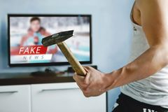 Truth misrepresented in the news on a modern TV. A psychopath wants to crash the TV with a hammer. The viewers got tired of false news. Truth misrepresented in stock image