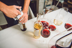 Truth in wine at table. Top view. Glasses, bottles and carafe with different sorts of wine. Man is opening flask stock photography