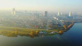 Trutnia latanie nad duża zmierzchu miasta sceneria, różnorodni budynki zbliża pięknych jeziornych brzeg i koloru żółtego jesieni  zdjęcie wideo