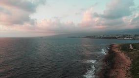 Trutnia latanie wzdłuż bezbrzeżnego oceanu z skalistym seashore i turysty zwyczajnym quay przy zmierzchem zbiory