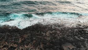 Trutnia odgórny widok seashore z czarną skalistą plażą i pięknym ogromnym morzem macha upadanie na falezach podczas burzy zbiory wideo