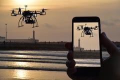 Trutnia quadrocopter, pilot do tv od smartphone, zmierzch nad dennym whit wieży obserwacyjnej tłem Obrazy Royalty Free