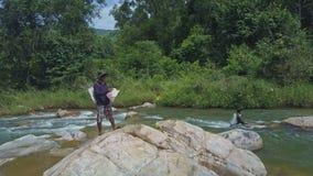 Trutnia widoku faceta stojaki na Rockowym mężczyzna Robią sposobowi przez rzekę zbiory
