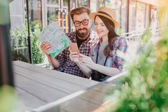 trvellers可爱的夫妇在手上的坐和看电话妇女举行 他们微笑 年轻人在手中拿着地图 库存图片
