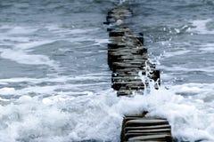 Trävågbrytare och vågor på Östersjön, kopieringsutrymme Arkivbild
