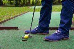 Trwa strzał piłka w kieszeni, mini kij golfowy, w górę, mężczyzna nogi zdjęcia stock