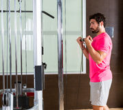 Trwanie bicepsa kabla kędzioru mężczyzna w pulley maszynie Zdjęcia Royalty Free