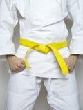 Trwanie myśliwskich koloru żółtego paska sztuk samoobrony biały kostium Obrazy Stock