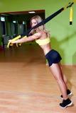 做TRX锻炼的美丽的少妇 免版税库存照片