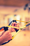 TRX. Female hands with fitness TRX straps in gym.  Stock Photography