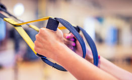 TRX. Female hands with fitness TRX straps in gym.  Royalty Free Stock Images