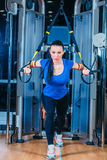 TRX. fitness, sports, exercise, technology and. Fitness, sports, exercise, technology and people concepts - smiling young woman doing exercise at the gym Royalty Free Stock Image
