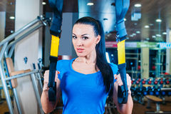 TRX. fitness, sports, exercise, technology and. Fitness, sports, exercise, technology and people concepts - smiling young woman doing exercise at the gym Stock Photos