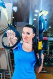 TRX. fitness, sports, exercise, technology and. Fitness, sports, exercise, technology and people concepts - smiling young woman doing exercise at the gym Stock Images