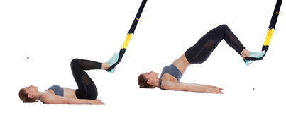 TRX hip press. Athletic woman performing a functional exercise with suspension cable Stock Photos