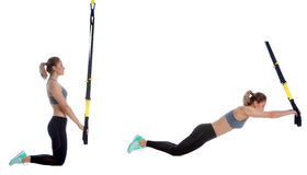 TRX kneeling rollout. Athletic woman performing a functional exercise with suspension cable Stock Photos