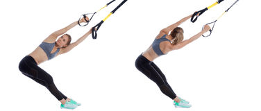 TRX lower back stretch. Athletic woman performing a functional exercise with suspension cable Royalty Free Stock Photos