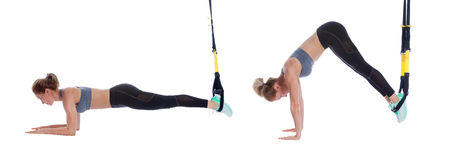 TRX pike exercise. Athletic woman performing a functional exercise with suspension cable Stock Images