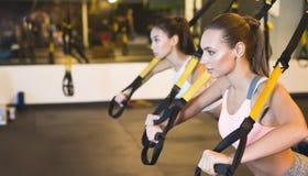 Trx szkolenie Dziewczyny trenuje triceps z sprawności fizycznych patkami obraz stock
