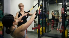 TRX training. A girl with a beautiful figure pulls up on the belts. Nearby there is a coach 4K Slow Mo stock video footage