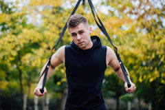 TRX training. Man Instructor at the park doing Excersise. Fitness workout. Royalty Free Stock Photos