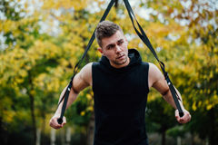 TRX training. Man Instructor at the park doing Excersise. Fitness workout. Stock Image