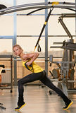 TRX training. Young attractive woman training with htrx fitness straps in the gym's studio royalty free stock photography