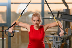 TRX training. Young attractive woman training with htrx fitness straps in the gym's studio Stock Photo