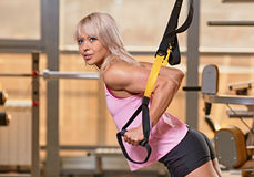 TRX training. Young attractive woman training with htrx fitness straps in the gym's studio royalty free stock photos