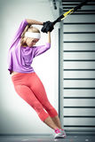 TRX training. Young woman streching muscles TRX training Stock Photography