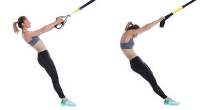 TRX upper back stretch. Athletic woman performing a functional exercise with suspension cable Stock Photo